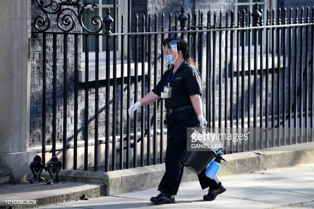 A cleaner in PPE arrives at 10 Downing Street the official residence of Britain's Prime Miniser in central London on April 16 2020 The British...