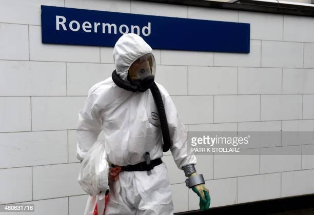 A cleaner in protective clothing searches for asbestos fibers arround the train station in downtown Roermond Netherlands on December 18 2014 The...