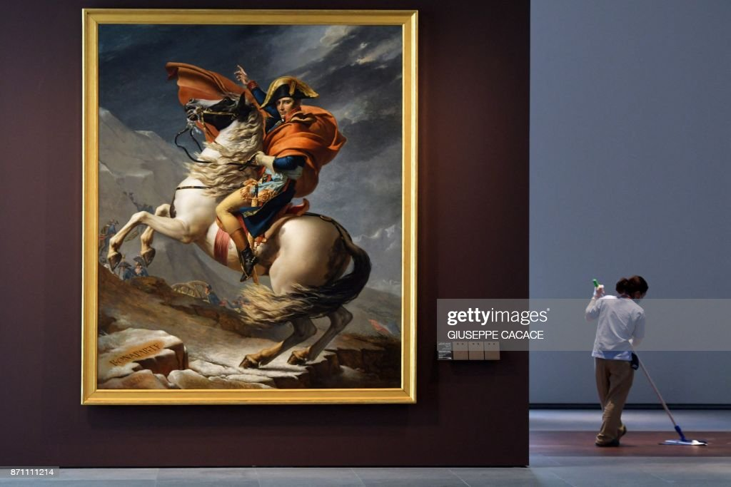 TOPSHOT - A cleaner mops the floor next to the painting titled 'Napoleon Bonaparte, First Consul, Crossing the Alps' by French artist Jacques-Louis David at the Louvre Abu Dhabi Museum during a media tour on November 6, 2017 prior to the official opening of the museum on Saadiyat island in the Emirati capital on November 8. More than a decade in the making, the Louvre Abu Dhabi opens its doors this week, bringing the famed name to the Arab world for the first time. The museum currently has some 300 pieces on loan, including an 1887 self-portrait by Vincent van Gogh and Leonardo da Vinci's 'La Belle Ferronniere'. /