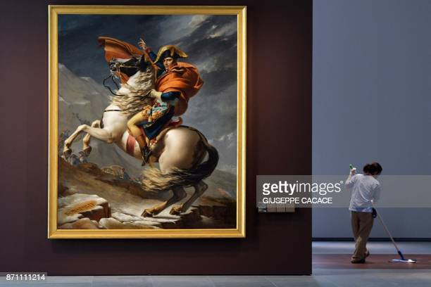 TOPSHOT A cleaner mops the floor next to the painting titled 'Napoleon Bonaparte First Consul Crossing the Alps' by French artist JacquesLouis David...