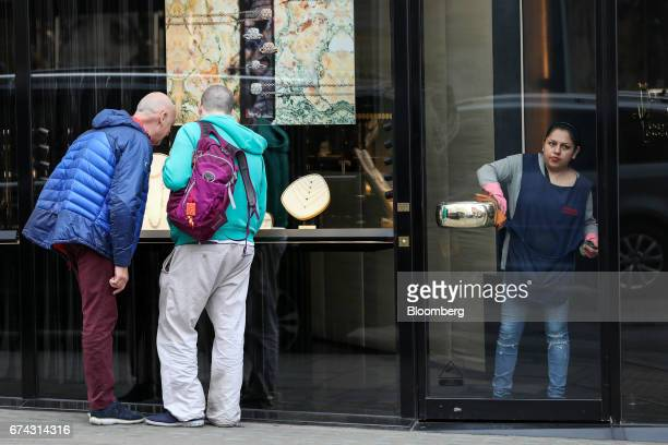A cleaner polishes the door handle of a luxury jewelery store on Bond Street in London UK on Thursday April 27 2017 LVMH Moet Hennessy Louis Vuitton...