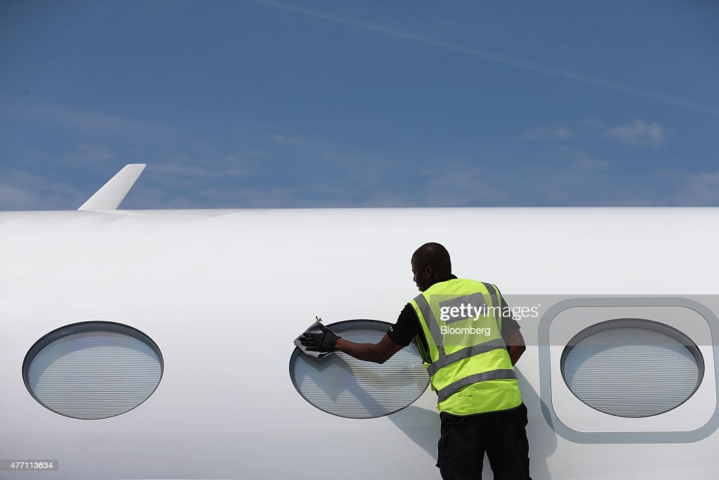 A cleaner polishes the passenger windows of a Gulfstream business jet, manufactured by Aerospace Corp., during preparations ahead of the 51st International Paris Air Show in Paris, France, on Sunday, June 14, 2015. The 51st International Paris Air Show is the world's largest aviation and space industry exhibition and takes place at Le Bourget airport June 15 - 21. Photographer: Jasper Juinen/Bloomberg via Getty Images