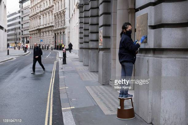 Cleaner polishing a brass plaque in the City of London on 29th January 2021 in London, United Kingdom. The financial district is home to many...