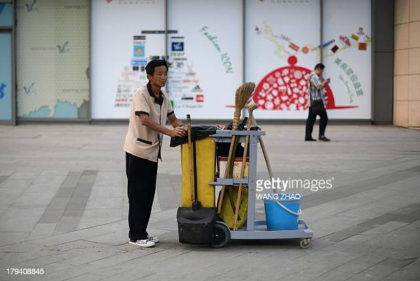 A cleaner pushes a cleaning trolley in front of a shopping mall in Beijing on September 3 2013 China lowered its figure for economic growth for last...