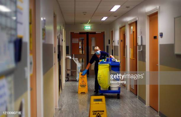 A cleaner pushes a cleaning trolley through the Critical Care Unit at The Royal Blackburn Teaching Hospital operated by East Lancashire NHS Trust in...