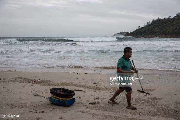 A cleaner rakes garbage on a beach in Hong Kong on October 15 2017 as Typhoon Khanun moved across the northern part of the South China sea / AFP...
