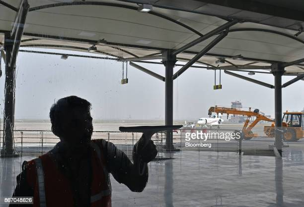 A cleaner removes excess water from a window at the newly inaugurated Terminal 2 building at the Indira Gandhi International Airport in Delhi India...