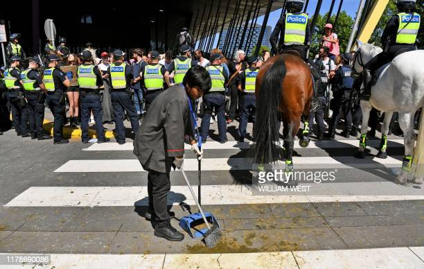 A cleaner sweeps up after police horses as climate change protesters attempt to blockade the International Mining and Resources Conference being held...