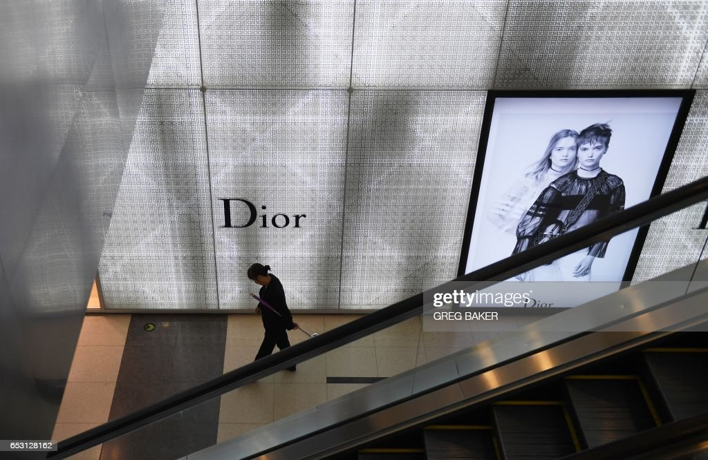 A cleaner walks past a luxury store at a shopping mall in Beijing on March 14, 2017. China retail sales growth decelerated to 9.5 percent year-on-year in January and February, government data showe...