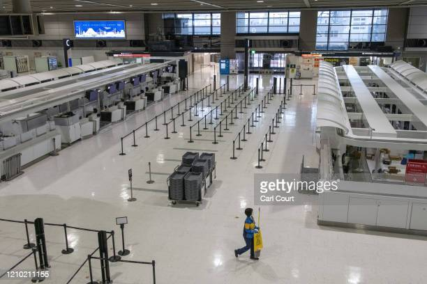 Cleaner walks past empty check-in desks at Narita Airport on April 17, 2020 in Tokyo, Japan. Narita Airport, one of Japans busiest, has closed one of...