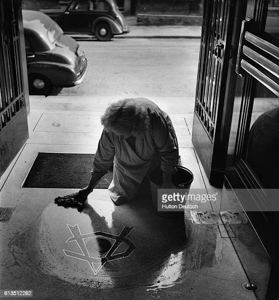 A cleaner washing the entrance hall to the Arsenal football club at Highbury in north London