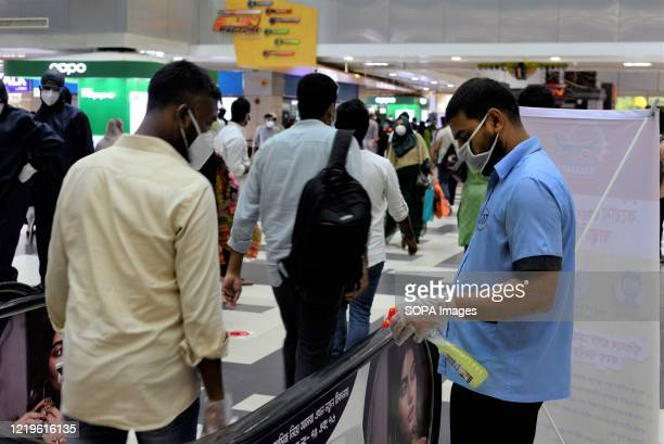 Cleaner wearing a face mask disinfects an escalator as a precaution against the spreed of coronavirus during the eased restrictions. Lockdown in...
