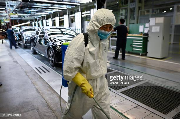 A cleaner wearing protective gear sprays disinfectant along a production line at a Mercedes Benz automotive plant during a media tour organised by...