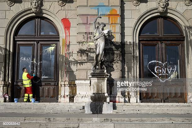 A cleaner wipes a window of the Grand Theatre de Geneve opera house on December 20 2015 in Geneva after it was vandalised during a demonstration the...