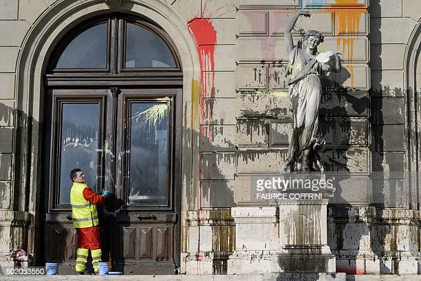TOPSHOT A cleaner wipes a window of the Grand Theatre de Geneve opera house on December 20 2015 in Geneva after it was vandalised during a...
