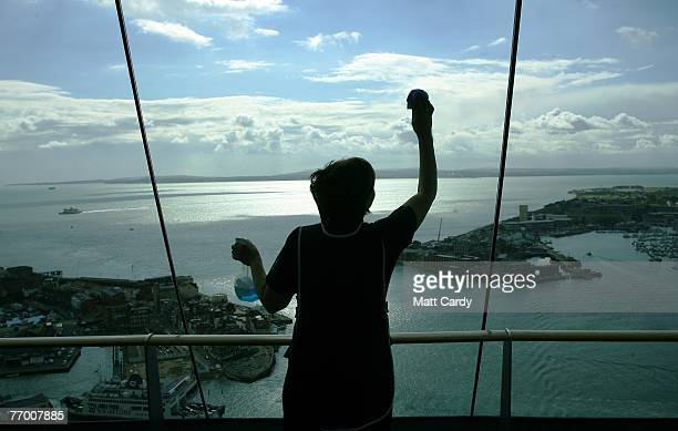 A cleaner wipes the windows inside the Spinnaker Tower on September 25 2007 in Portsmouth England Originally scheduled for completion in time for the...