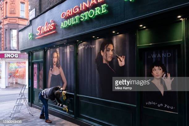 Cleaner wiping down the new exterior to Soho's Original Adult Store in Soho on 1st December 2020 in London, United Kingdom. Traditionally, this area...