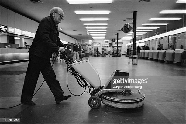A cleaner with an electric floor polisher at Luton Airport UK 1975