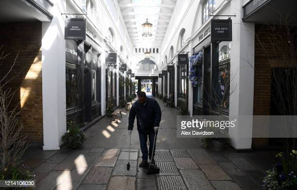 A cleaner works at an Empty Covent Garden on March 22 2020 in London England Coronavirus has spread to at least 188 countries claiming over 13000...