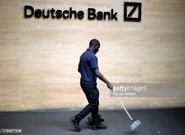 A cleaner works outside the offices of German bank Deutsche Bank in central London on July 8 2019 Germany's biggest lender Deutsche Bank said Sunday...