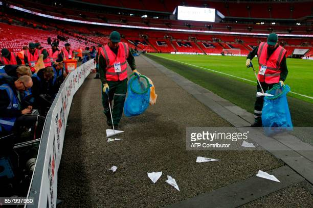 Cleaners collect paper aeroplanes thrown onto the pitch from the crowd during the FIFA World Cup 2018 qualification football match between England...