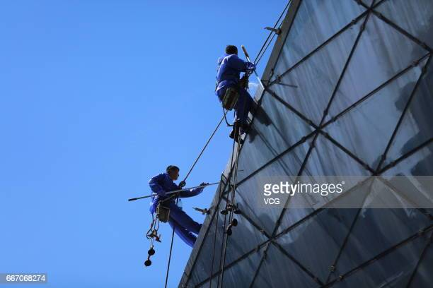 Cleaners dangle from rope to clean the glass of Shengjing Grand Theatre on April 11 2017 in Shenyang Liaoning Province of China More than 10 cleaning...