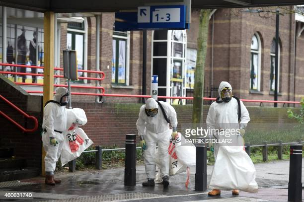 Cleaners in protective clothing search for asbestos fibers arround the train station in downtown Roermond Netherlands on December 18 2014 The center...