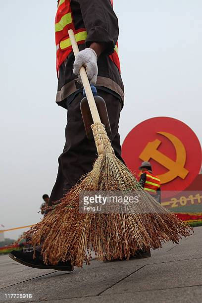 A cleaners passes by an emblem of the Communist Party of China on the Tiananmen Square on June 30 2011 in Beijing China This year's celebrations will...