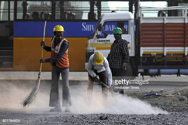 Cleaners remove dust at roadside ahead in order to control air pollution on November 8 2016 in Noida India Though the pollution level remains severe...