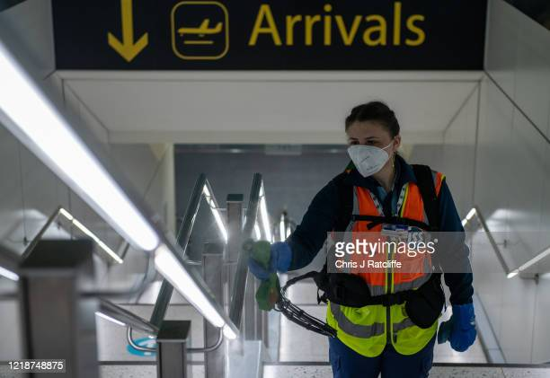 Cleaners spray a peroxide based disinfectant on handrails and surfaces as a protective measure against the spread of Covid19 inside the currently...