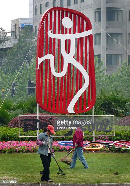 Cleaners sweep a lawn in front of the emblem of Beijing Olympics on the day marking the 100-day-countdown to the 2008 Olympic Games on April 30, 2008...