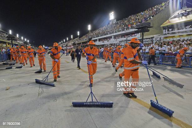 Cleaners sweep the Sambadrome during the second night of Rio de Janeiro's Carnival, in Brazil, on February 13, 2018. / AFP PHOTO / Carl DE SOUZA