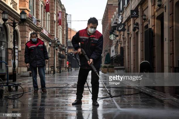 Cleaners wash the street with a high-pressure water gun on February 3, 2020 in Wuhan, Hubei province, China. The number of those who have died from...