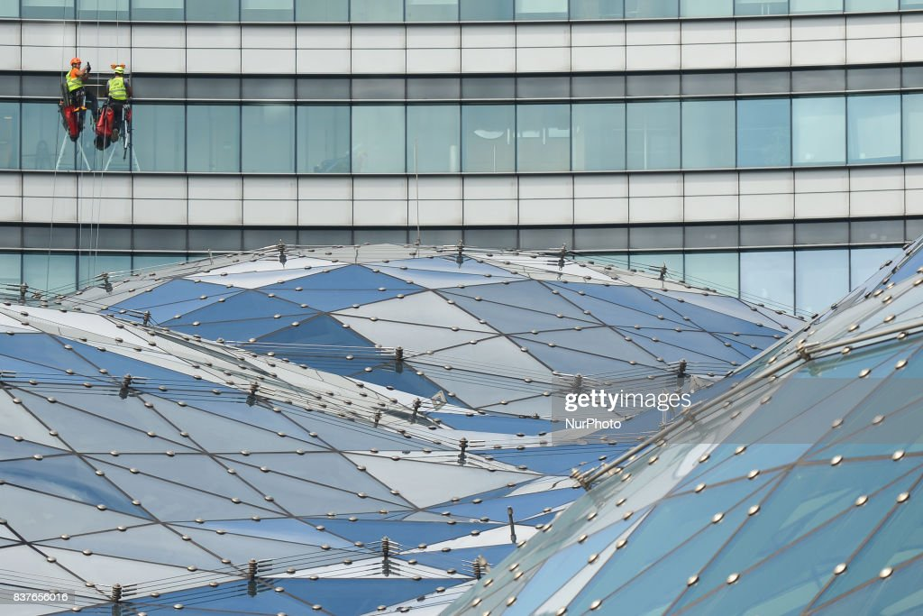 Cleaners work on the facade of 'The Zote Tarasy' commercial, office, and entertainment complex in the center of Warsaw, located next to the Warszawa Centralna railway station. On Tuesday, August 21, 2017, in Warsaw, Poland.