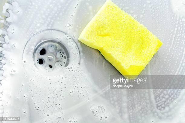 Limpieza un lavamanos con esponja amarilla