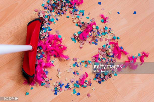 cleaning confetti and pink feathers after party on hardwood floor - cleaning after party stock pictures, royalty-free photos & images