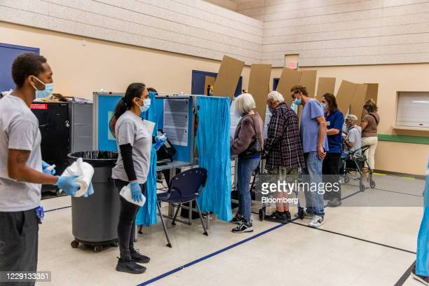 Cleaning crew stands by as voters cast ballots at an early voting polling location for the 2020 Presidential elections in Las Vegas, Nevada, U.S., on...