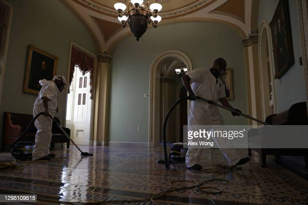 Cleaning crew vacuums the floor of a hallway at the U.S. Capitol January 7, 2021 in Washington, DC. The U.S. Congress has finished the certification...