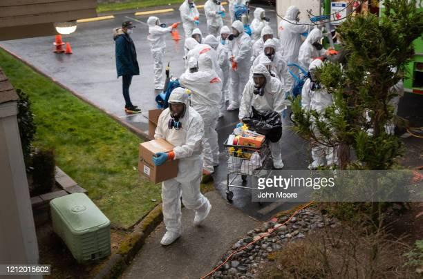 A cleaning crew wearing protective clothing takes disinfecting equipment into the Life Care Center on March 12 2020 in Kirkland Washington The...