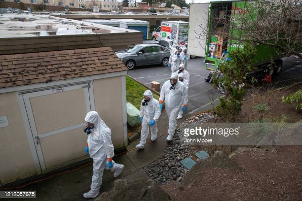 A cleaning crew wearing protective clothing to protect them from coronavirus enters the Life Care Center on March 12 2020 in Kirkland Washington The...