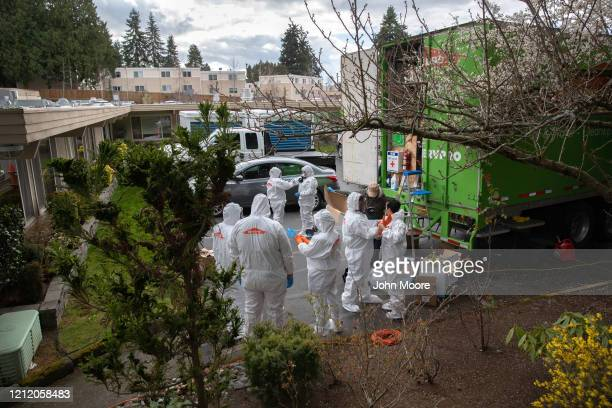 A cleaning crew wearing protective clothing to protect them from coronavirus prepares to enter the Life Care Center on March 12 2020 in Kirkland...