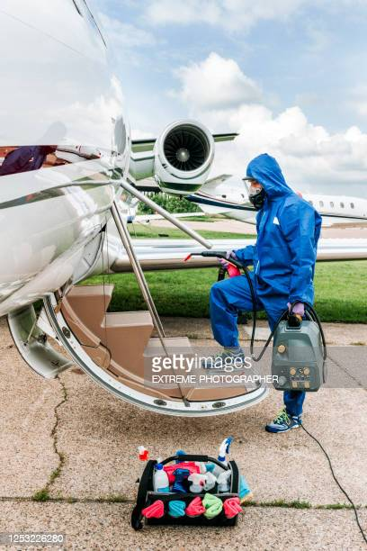 a cleaning crewman in coveralls sterilizing the boarding stairs of a small private jet parked on an airport taxiway during the covid-19 pandemic - department of health stock pictures, royalty-free photos & images