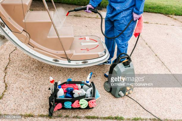 a cleaning crewman spraying down the cleaning fluid on the boarding stairs of a small private jet during coronavirus epidemic - department of health stock pictures, royalty-free photos & images