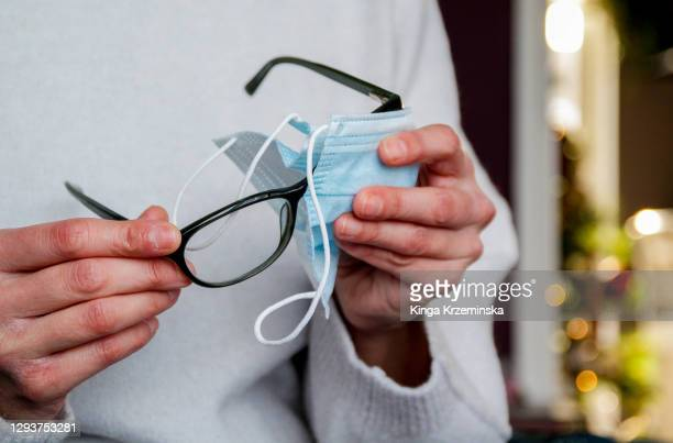 cleaning glasses with face covering - misinformation stock pictures, royalty-free photos & images