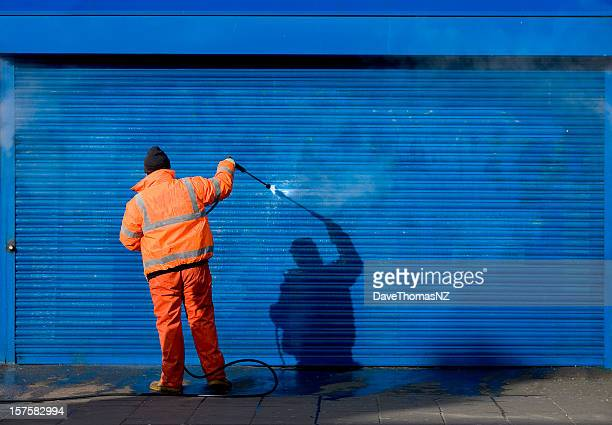 Cleaning graffiti off a security grill.