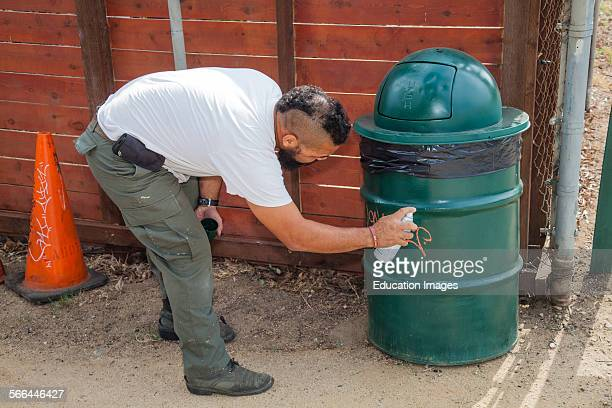 Cleaning graffiti off trash can along the banks of the Los Angeles River in the Glendale Narrows, Los Angeles, California.
