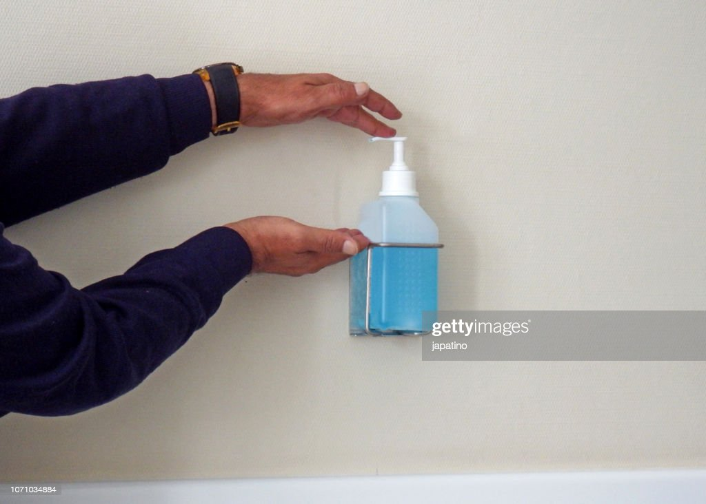 Cleaning hands with disinfectant liquid : Stock Photo