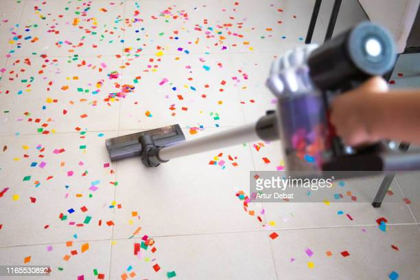 cleaning home floor with vacuum after party with confetti. - after party stockfoto's en -beelden