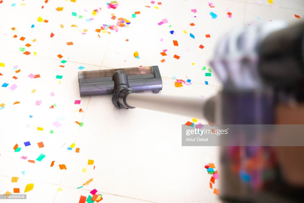 Cleaning home floor with vacuum after party with confetti. : Stock Photo