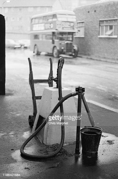 A cleaning hose at Stockwell Bus Garage south London 26th February 1967 In the background is a Leyland Titan doubledecker bus
